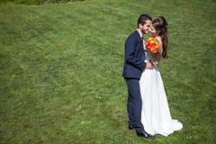 Dans l'épouse et le marié d'amour sur le champ d'herbe dans le jour d'été ensoleillé Photos libres de droits