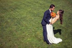 Dans l'épouse et le marié d'amour sur le champ d'herbe dans le jour d'été ensoleillé Images stock