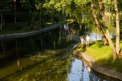 Dans l'amour la paire marche en parc près du lac Photos libres de droits