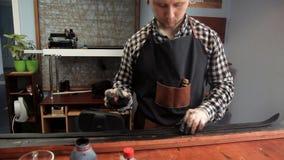 Dans l'atelier, un spécialiste colore la ceinture dans le noir Procédure pour la fabrication des ceintures en cuir banque de vidéos