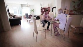 Dans l'homme attirant de chambre légère et la blonde mignonne reposez-vous à la table et buvez les boissons banque de vidéos