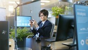 Dans l'homme d'affaires asiatique est Plays Video Games de bureau sur son SM photographie stock