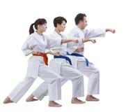 Dans l'homme de karategi et deux femmes battent le bras de poinçon d'isolement Images stock