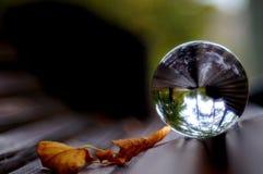 Dans la boule de cristal magique observant le ciel d'automne images stock