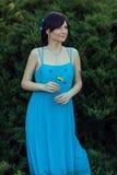 Dans la fille de jardin d'été dans une robe bleue Images libres de droits