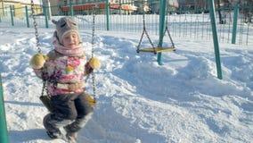 Dans la fille de parc d'hiver sur une oscillation
