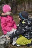 Dans la forêt, le garçon demande la rémission de la fille Image libre de droits