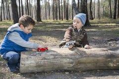 Dans la forêt, se reposant sur un rondin, deux garçons, on jouant avec a à Photographie stock libre de droits