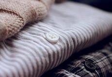 Dans la pile est un grand choix d'écharpe et de chemises beiges de laine de vêtements-un image libre de droits