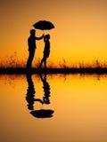 Dans la réflexion d'amant de l'homme et de la femme tenant le parapluie en silhouette de coucher du soleil de soirée Photo stock