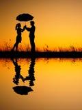 Dans la réflexion d'amant de l'homme et de la femme tenant le parapluie en silhouette de coucher du soleil de soirée Photographie stock libre de droits