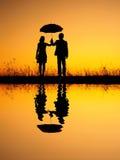 Dans la réflexion d'amant de l'homme et de la femme tenant le parapluie en silhouette de coucher du soleil de soirée Photographie stock