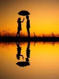 Dans la réflexion d'amant de l'homme et de la femme tenant le parapluie en silhouette de coucher du soleil de soirée Photos libres de droits