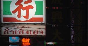 Dans la soirée dans les signes vus par rue et l'enseigne lumineux et brillants d'un restaurant local clips vidéos