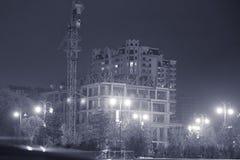 Dans la soirée le bâtiment va être construit Silhouettez la grue de bâtiment et le bâtiment en construction contre égaliser le ci Images stock
