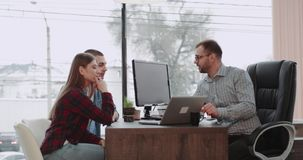 Dans le beau bureau panoramique jeunes des couples ont une réunion avec leur directeur d'agence d'agent immobilier ou pour obteni banque de vidéos