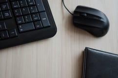 Dans le bureau, clavier de souris et table de carnet Image stock