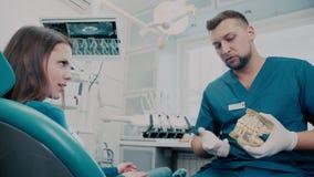 Dans le bureau de The de dentiste un patient demande au dentiste de questions clips vidéos