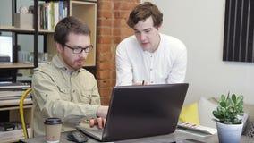 Dans le bureau, deux jeunes hommes travaillent devant l'ordinateur clips vidéos