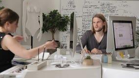 Dans le bureau la femme montre un objet large devant l'homme avec des gestes clips vidéos