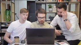 Dans le bureau, trois hommes travaillent tranquillement devant un ordinateur banque de vidéos