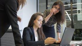 Dans le bureau trois les jeunes femmes ont l'amusement devant l'ordinateur portable sur le bureau banque de vidéos