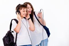 Dans le frère et la soeur écoutez la musique avec des écouteurs Photos libres de droits