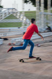 Dans le garçon de mouvement marchant sur un longboard avec un T-shirt rouge et des blues-jean Images stock
