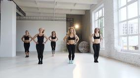 Dans le groupe a de classe de forme physique de six jeunes femmes dans les costumes noirs de sports exécutez les exercices de for banque de vidéos
