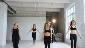 Dans le groupe a de classe de forme physique de six jeunes femmes dans les costumes noirs de sports exécutez les exercices sautan banque de vidéos