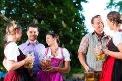 Dans le jardin de bière - amis buvant de la bière Photographie stock libre de droits