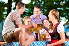 Dans le jardin de bière - amis buvant de la bière Image libre de droits