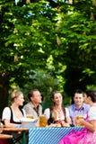 Dans le jardin de bière - amis sur une table avec de la bière Photographie stock libre de droits