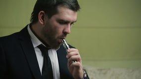 Dans le jeune homme d'affaires élégant ne travaille pas la cigarette électronique banque de vidéos