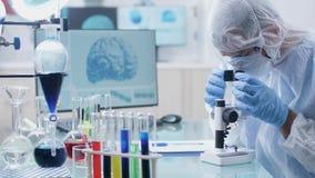Dans le laboratoire moderne et ? extr?mit? ?lev? de s?curit? un scientifique regarde dans le microscope clips vidéos