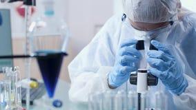 Dans le laboratoire moderne le scientifique dans la combinaison regarde dans le microscope clips vidéos