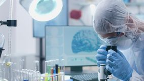 Dans le laboratoire moderne le scientifique dans la combinaison regarde par un microscope banque de vidéos