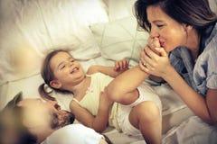 Dans le lit avec la maman et le papa ! photographie stock