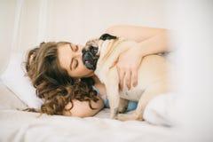 Dans le lit avec le petit chien mignon Jeune femme dans la chambre à coucher légère jouant avec son animal familier Image libre de droits