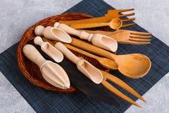Dans le panier est un ensemble de divers cuillères, scoops et fourchettes en bois photos stock