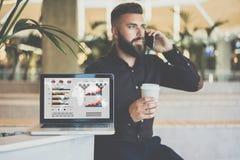 Dans le premier plan est l'ordinateur portable avec des graphiques, des diagrammes et des diagrammes sur l'écran Photographie stock