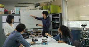 Dans le professeur de classe de l'informatique parlant aux étudiants au sujet de la technologie de robot