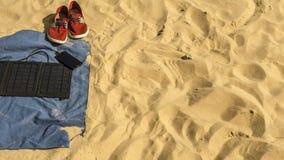 Dans le sable sur la plage soyez : serviette, espadrilles, un téléphone qui est chargé d'une batterie de panneau solaire Image libre de droits
