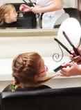 Dans le salon de coiffure. Enfant de petite fille s'asseyant par le coiffeur peignant des cheveux Images libres de droits