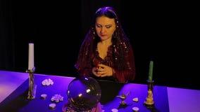 Dans le salon magique par lueur d'une bougie, cartes gitanes d'un fortunetelling de pass traînants banque de vidéos