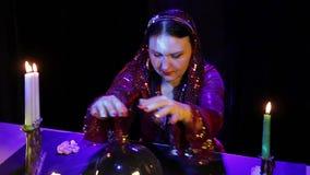 Dans le salon magique par lueur d'une bougie, un gitan lit l'avenir dans une boule de miroir dans la lueur des bougies banque de vidéos