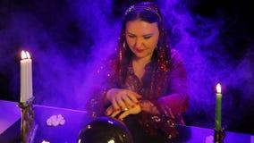 Dans le salon magique par lueur d'une bougie, un gitan lit l'avenir dans une boule de miroir parmi des nuages de fumée clips vidéos