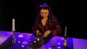 Dans le salon magique par lueur d'une bougie, un gitan se demande sur les cartes banque de vidéos