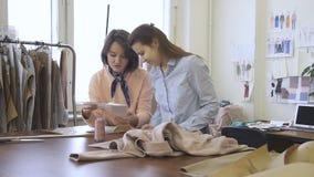 Dans le studio de couture deux les spécialistes sélectionnent des accessoires pour l'habillement de couture du ` s de femmes banque de vidéos