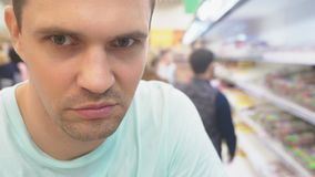 Dans le supermarché, un plan rapproché du visage du mari qui attend son épouse tandis qu'elle fait des emplettes au magasin alésé clips vidéos